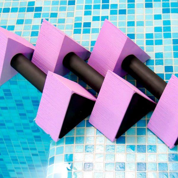 three pink aqua dumbbells lie on the coast swimming-pool
